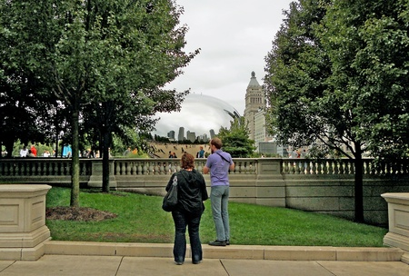 comtemporary: Tourists in Millennium Park view the Chicago skyline in the Cloudgate sculpture, fondly known as The Bean.