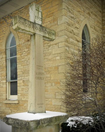 memorial cross: World War II Memorial croce a fianco della chiesa, costruzione calcare, finestre ad arco gotico. Salici nelle vicinanze proclamare che la vita continua anche nella neve d'inverno.