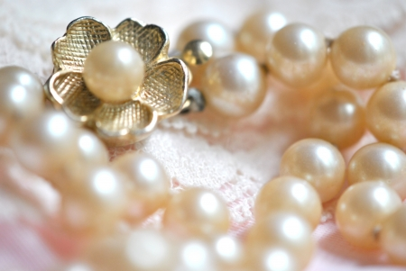 Pearl necklace with gold flower clasp on lace fabric. Shallow DOF