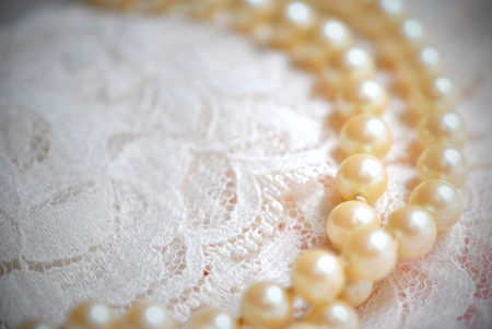 Pearl necklace on lace fabric. Stock Photo