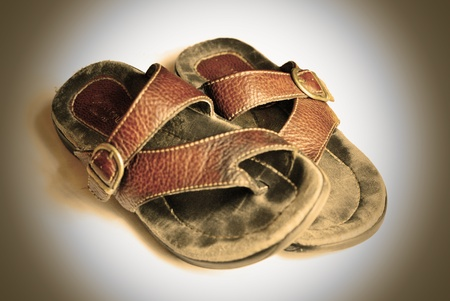 liesure: A well-worn pair of leather thong sandals. Sepia effect.