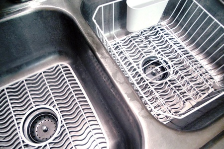 double sink: Double bowl kitchen sink with white mats and dish drainer.