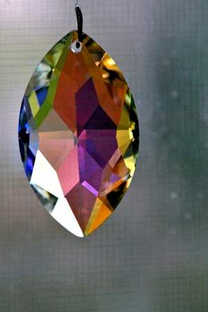 Cut lead crystal prism dangling before a dull window. Stock Photo