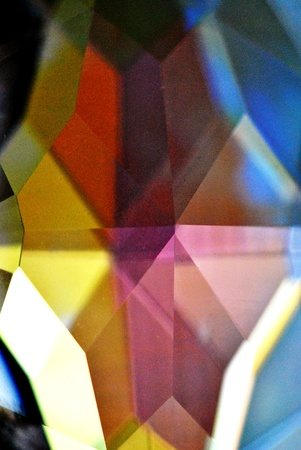 Cut lead crystal prism; extreme closeup.  Colorful background.