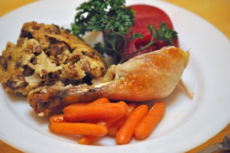 holiday meal: Roast chicken drumstick, dressing, carrots, and spiced apple rings: a traditional holiday meal served up on a white glass plate. Stock Photo
