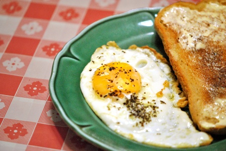 Fried egg, sunny side up, with basil garnish and a slice of hot buttered toast, on a green plate. photo