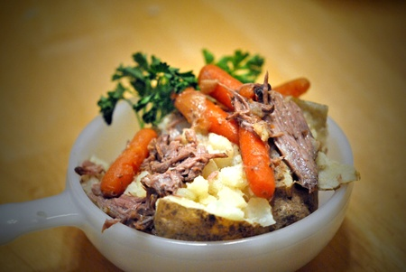 Baked potato topped with beef and carrots and garnished with parsley