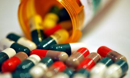 Pills spilling from a prescription medicine bottle.  Shallow DOF. Stock Photo - 12394406