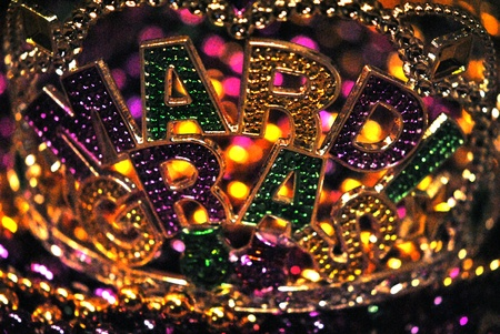 Mardi Gras spelled out in glittering green, gold, and purple letters.  Shallow DOF, bokeh.