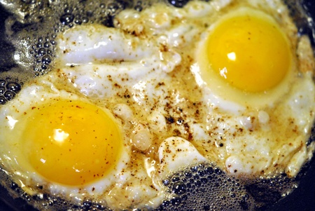Two eggs frying in bacon fat