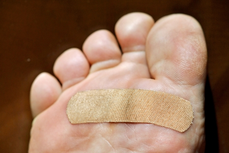 bandaged: Bandage over a painful wound on the bottom of the ball of the foot