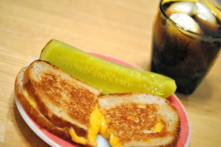 A simple lunch for Lent or any time   grilled cheese sandwich, dill pickle, and a fizzy iced beverage. Stock Photo