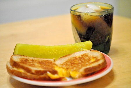 A simple lunch for Lent or any time   grilled cheese sandwich, dill pickle, and a fizzy iced beverage  Stock Photo