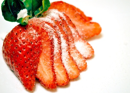 Sliced strawberry sprinkled with sugar on a white background   Plenty of copy space