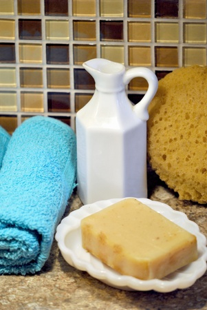 Bath and spa supplies;  towels, soap, sponge, and pitcher of bath oil  photo