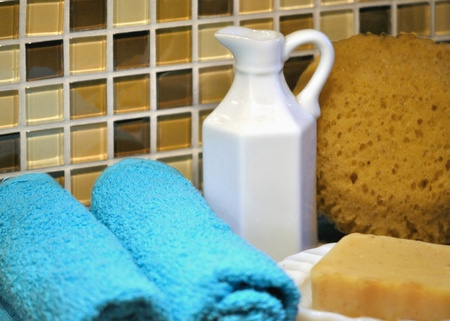 self indulgence: Bath and spa supplies;  towels, soap, sponge, and pitcher of bath oil  Stock Photo