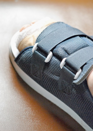 Injured foot with bandages and orthopedic shoe