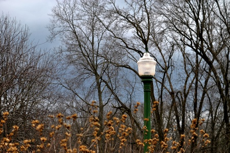 As skies darken and the storm threatens, a lamplight guides travelers safely along the road home Stock Photo - 12803381