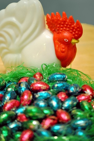 Candy easter eggs in a nest guarded by a hen figurine  photo