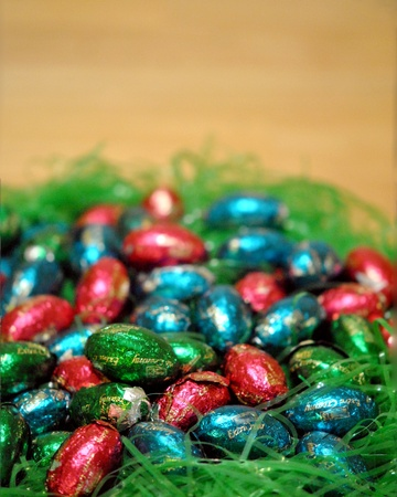 Chocolate candy easter eggs in a nest of decorative grass Stock Photo - 12803685