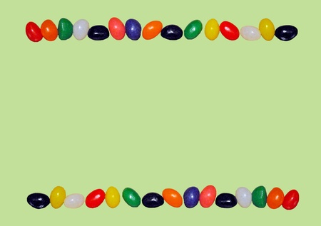 Top and bottom borders of jelly beans in bright colors isolated on a pastel green background  Stock Photo