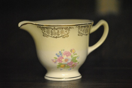 crazed: A china cream pitcher with delicate floral pattern and gilded rim and border design, but slightly crazed glazing