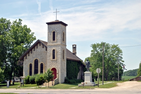 congressman: Built in 1867 of the native yellow limestone, this church is covered with ivy right up to the decorative wooden carvings at the roof eaves   A statue of a local statesman stands at the street corner  Stock Photo