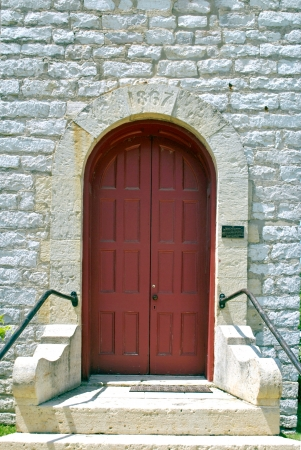 An arched red church door in a limestone wall; the keystone is dated 1867. Stock Photo