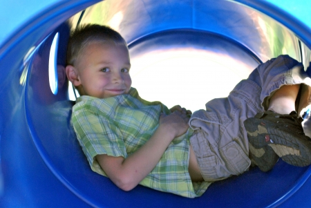 Mischievous grin on his face, the young boy is curled up inside the playground tunnel