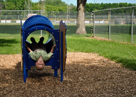 A young boy emerging from the play tunnel on his back, head upside-down  photo