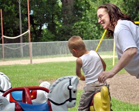 Happy woman playing with child on playground carousel