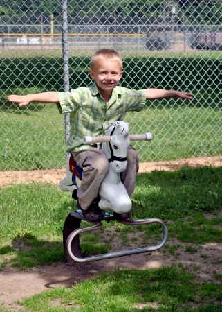 Look, Ma, no hands    Young boy rides the playground horse wihout holding on  photo