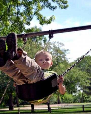 Peut-être la plus ancienne de l'équipement de jeux de tous, le swing offre un moment de l'exercice pacifique douce pour le jeune garçon Banque d'images