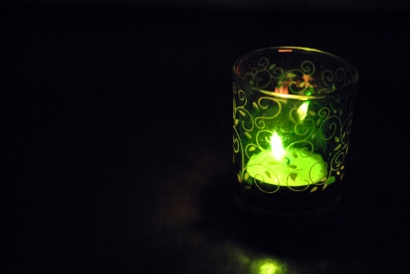 votive candle: Votive candle in green glass with gold floral vine tracery   Plenty of copy space  Stock Photo
