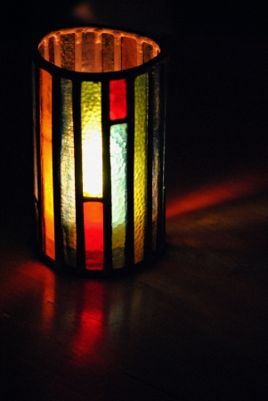 Stained glass lamp chimney shields a candle from breeze and adds a splash of color to the wooden table  Stock Photo - 14921454