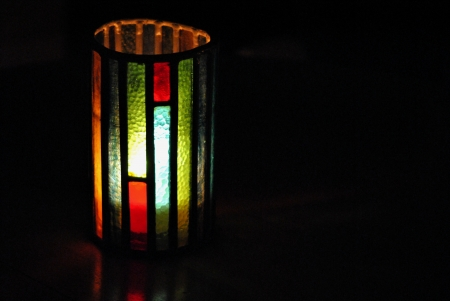 hurricane lamp: Stained glass lamp chimney shields a candle from breeze and adds a splash of color to the wooden table