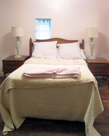 Dainty and feminine without much fuss, pink and white quilts, blankets, and pillow shams are the centerpiece of this lovely bedroom  photo