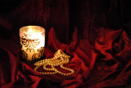 Pearl necklace and candle on red velvet background  Stock Photo - 16420061