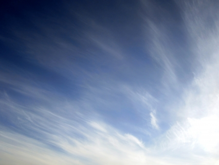 Wispy white cirrus clouds in a deep blue sky  Фото со стока