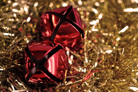 Two jingle bells nestling into a bed of gold tinsel  Stock Photo