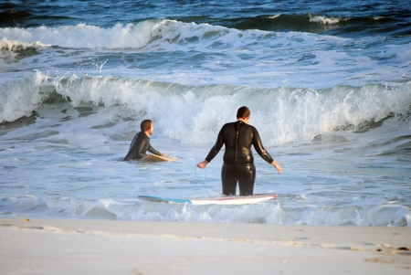 Surfers head out looking for that perfect wave   Pensacola Beach, Florida, USA in mid-winter Stock Photo - 17594081