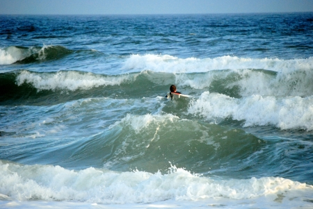 Surfer heads out to catch a wave in the blue-green waters of the Gulf of Mexico Stock Photo - 17594082