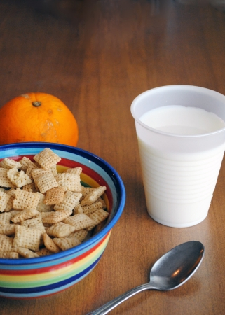 A simple light summer breakfast, a bowl of cereal, a glass of milk, and a piece of fruit   Shallow DOF  Imagens