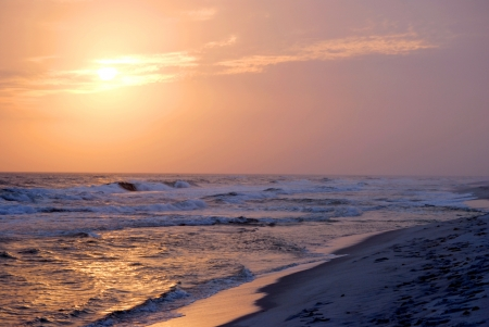 A winter sunset floods the beach with purple and gold; Pensacola Beach, Florida