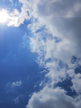 Clouds in a deep blue sky with sun peeking through; lens flare effect