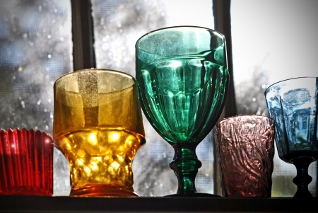 Collection of vintage glassware on the shelf in the window of the old house  photo