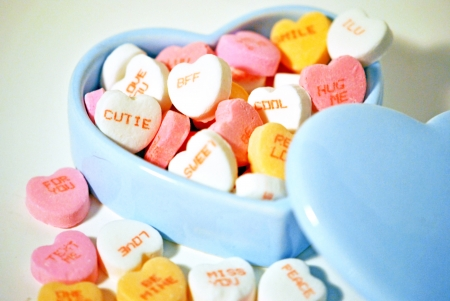 Valentine candy hearts with messages in a blue ceramic box  photo