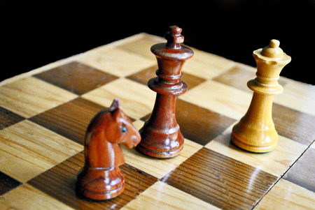 Carved chess pieces and board; white queen and black king and knight
