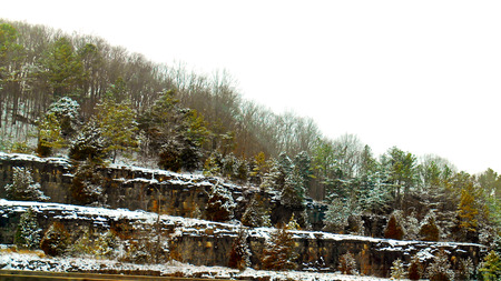 Cuts through the hillside permit the passage of the interstate highway; snow-covered evergreens decorate the landscape