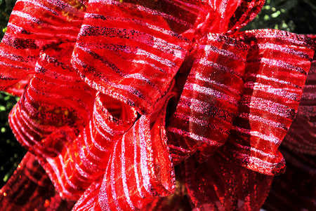 Gauzey red ribbon bow with silvery glitter stripes makes a festive decoration.
